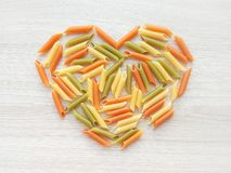 Textured Italian food background - colorful uncooked penne pasta heart shape on wooden table. Top view flat lay close up photography. Love pasta concept royalty free stock photography
