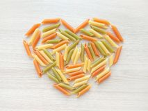 Textured Italian food background - colorful uncooked penne pasta heart shape on wooden table stock photos