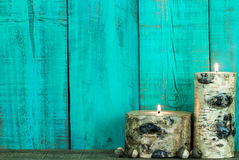 Textured log candles burning by antique green background Stock Images