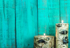 Textured log candles burning by antique teal blue wooden wall Royalty Free Stock Images