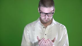 A textured man with a stubble and glasses examines his palms on a green background stock video footage