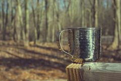 Textured metal mug in woods on sunny day stock photography