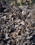 Textured obsidian on a hill in the forest. A textured and layered hill of obsidian rocks at the Big Obsidian Flow in the Newberry National Volcanic Monument in Stock Images