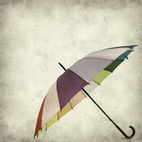 Textured old paper background. With multicolored umbrella Royalty Free Stock Photography