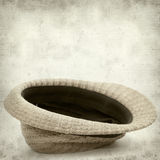 Textured old paper background. With old broken panama straw hat stock photography