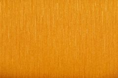 Textured orange wallpaper with a yellow tin royalty free stock image