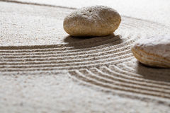 Textured pebbles across sinuous waves for spirituality Stock Photos