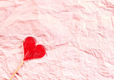 Textured pink crinkled paper Valentines background. With a red heart-shaped lollipop in one corner and plenty of copy space for a message to a loved one Royalty Free Stock Images