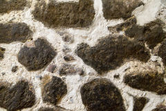Textured stone walls built of large rough stones held together by dark lumps Royalty Free Stock Images