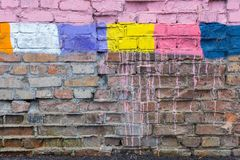 Textured surface of a brick wall with multicolored spots Royalty Free Stock Photos