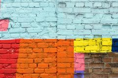 Textured surface of a brick wall with multicolored spots Stock Images