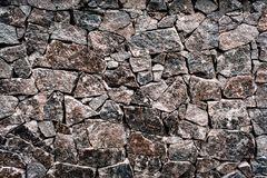 Textured texture of an old stone wall. Wallpaper for background and design. Textured texture of a dark and gray old stone wall. Wallpaper for background and stock photography