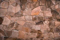 Textured texture of an old stone wall. Wallpaper for background and design. Textured texture of a light brown, old stone wall. Wallpaper for background and stock image