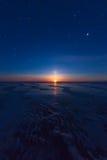 Textured tile blue ice hummock of Lake Baikal at moon light. Olk Royalty Free Stock Image