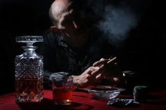 Man smoke pipe and play poker. Textured very old man with a straight face in the form of a player from the ranch stock image