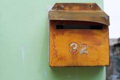 Textured vintage orange postbox on green wall Stock Photo