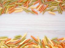 Textured Włoski karmowy tło - kolorowy uncooked penne makaron na drewnianym stole zdjęcie stock