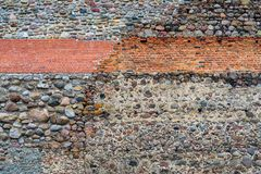 Textured wall background from stones and bricks. The abstract textured background of an old wall in vintage style from stones and bricks royalty free stock image