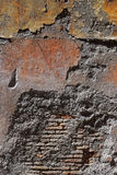 Textured wall with exposed brick. In red and oranges. Found in Rome, Italy Stock Photos