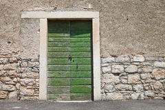 Textured wall with green door Stock Images