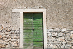 Textured wall with green door Royalty Free Stock Photo