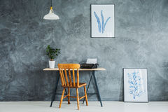 Two posters with sketches. Textured wall with two posters with blue sketches and minimal desk with wooden chair royalty free stock image
