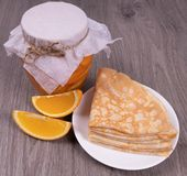 On a textured wooden background, a jar of orange syrup next to it is a plate of pancakes and sliced orange slices stock photography