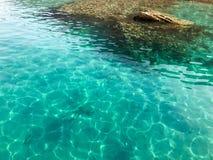 Texturen är salt vatten för det genomskinliga våta blåa ljusa regnbågsskimrande havet, havet, havet med vågor, krusningar med bot royaltyfri foto