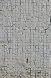 Texturen av den gamla betongväggen, med en beläggning av grunda tegelplattor av fyrkantig form, målade i grå färger Bakgrundsbild arkivbilder