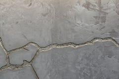 Texturen av den gr?a betongv?ggen dekoreras med en djup spricka av silverf?rg arkivfoton