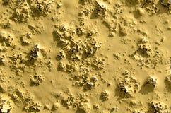 Texturen av den gula gamla målarfärgen på stenen Arkivbild