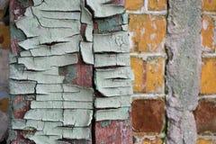 Texturen av det gamla spruckna trät som målas i blått på en bakgrund av en gammal tegelstenvägg Gammal sprucken målarfärg i skal Royaltyfri Foto