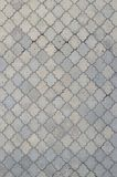 Texturen av en rytmisk mosaik som göras av konkreta tegelplattor Bakgrundsbild av ett stort område av den gamla och skadade grå f arkivbilder