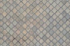 Texturen av en rytmisk mosaik som göras av konkreta tegelplattor Bakgrundsbild av ett stort område av den gamla och skadade grå f royaltyfri fotografi