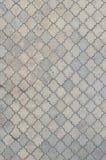 Texturen av en rytmisk mosaik som göras av konkreta tegelplattor Bakgrundsbild av ett stort område av den gamla och skadade grå f royaltyfri bild