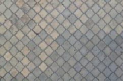 Texturen av en rytmisk mosaik som göras av konkreta tegelplattor Bakgrundsbild av ett stort område av den gamla och skadade grå f fotografering för bildbyråer
