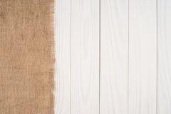 Texturen av säckväv på trätabellen för vit bakgrund Arkivbilder