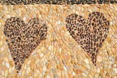 Texturen av stenväggen, vägen från liten runda och ovalstenar med gjorde sammandrag linjer av modeller av två sandiga hjärtor royaltyfria bilder