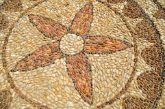Texturen av stenväggen, vägen från liten runda och ovalstenar med gjorde sammandrag modeller av blommamodeller arkivbild
