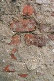Texturen av tegelstenväggen som täckas med betong som strös in med små flodstenar Arkivbild