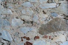 Texturen av väggen med olika lappar av marmor, granit, tegelsten arkivfoto
