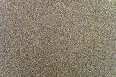 Textureof wet surface of the coating of bitumen roll roofing waterproofing. With the sprinkling of stone chips. Roofing background close-up stock image