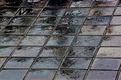 Texturer och mörker- och ljusreflexioner på våta tegelplattor Royaltyfri Bild