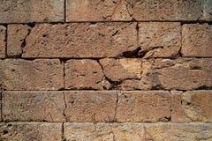Texturera bakgrund av den spruckna gamla naturliga stentegelstenväggen i guling med gemensam och grov yttersida Royaltyfri Bild