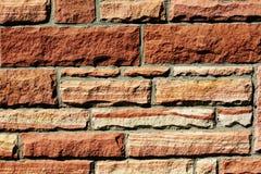 Texturera bakgrund av en vägg för röd sandsten arkivfoton