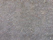 Texturera bakgrund som den gråa väggen som besprutade med små stenpartiklar royaltyfri foto