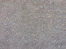 Texturera bakgrund som den gråa väggen som besprutade med små stenpartiklar Arkivfoton