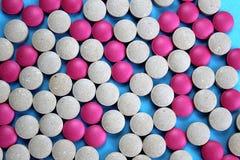 Texturera pillret som är rosa och som är grått på blå bakgrund arkivbild