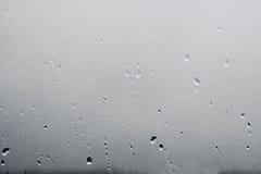 Texturera regndroppar på fönsterexponeringsglas för regn, svartvita färger, fotoet, ovanlig bakgrund arkivbilder