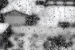 Texturera regndroppar på fönsterexponeringsglas för regn, svartvita färger, fotoet, ovanlig bakgrund royaltyfri foto